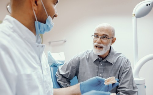 Elderly patient speaking with dentist in the practice