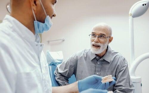 Elderly patient speaking with dentist in the practice