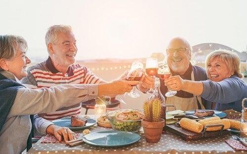 Group of fun elderly folks clinking glasses over dinner outdoors